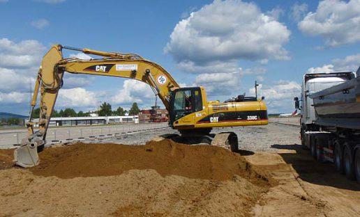 Gul gravemaskin graver i jord på Gardemoen